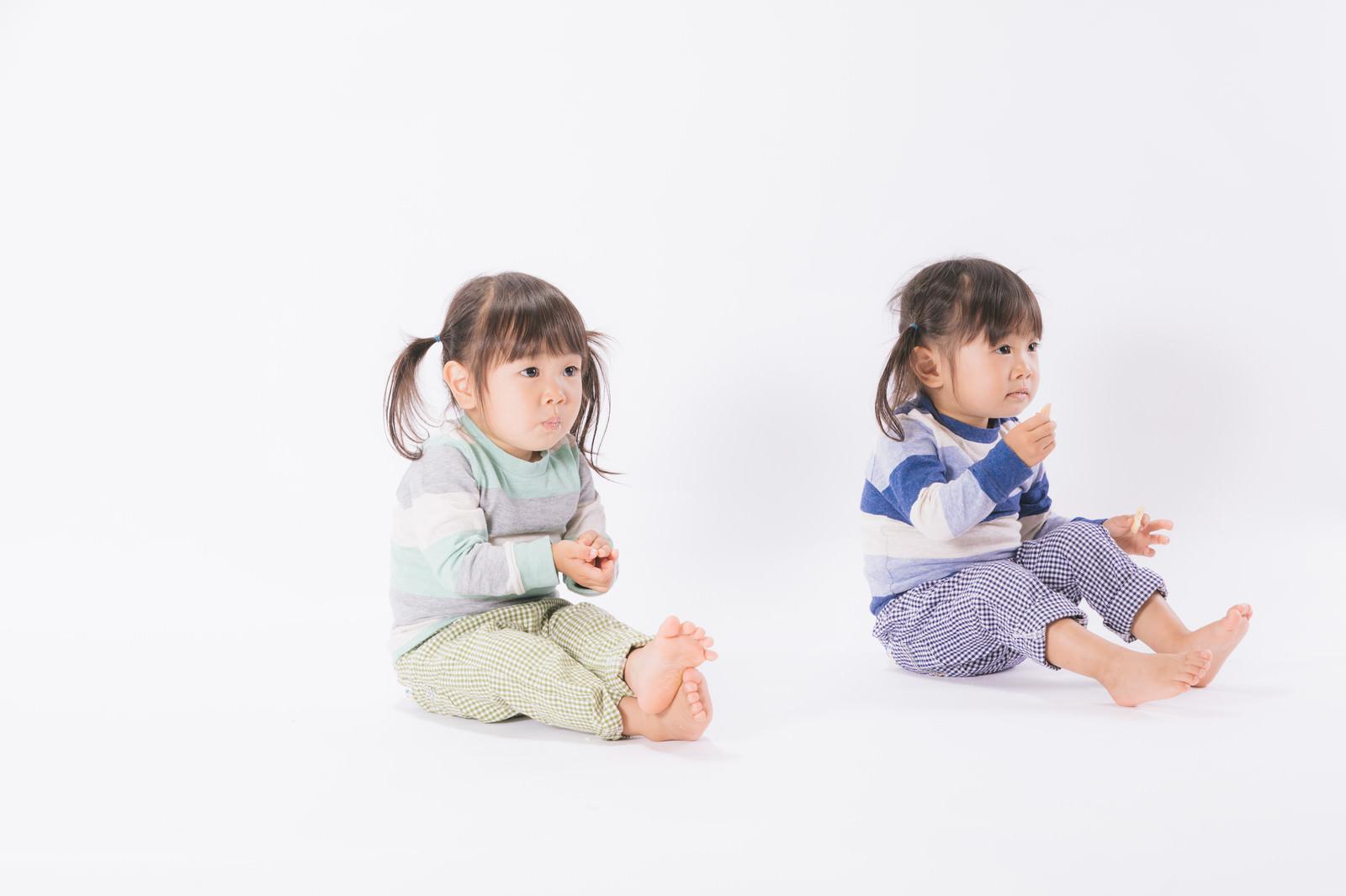 「お菓子を与えるとおとなしくなる子供たち(双子)」の写真[モデル:あおみどり]