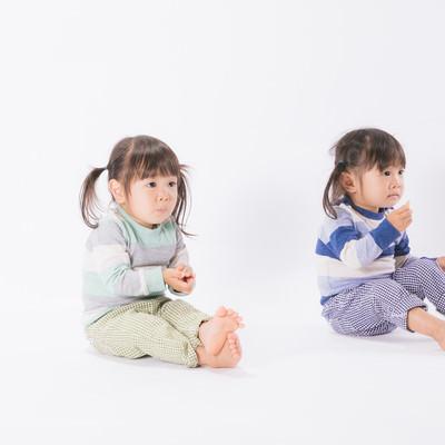 「お菓子を与えるとおとなしくなる子供たち(双子)」の写真素材