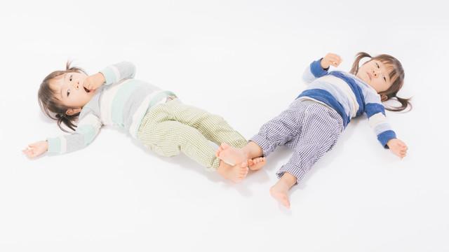 寝転ぶ姿も一緒の双子姉妹の写真
