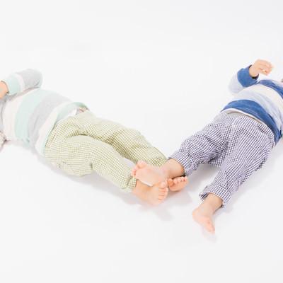 「寝転ぶ姿も一緒の双子姉妹」の写真素材
