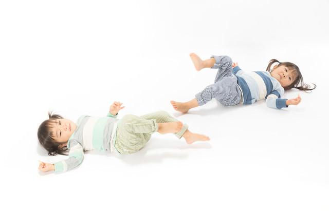 足上げてイヤイヤする双子の子供の写真