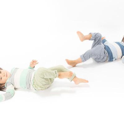「足上げてイヤイヤする双子の子供」の写真素材