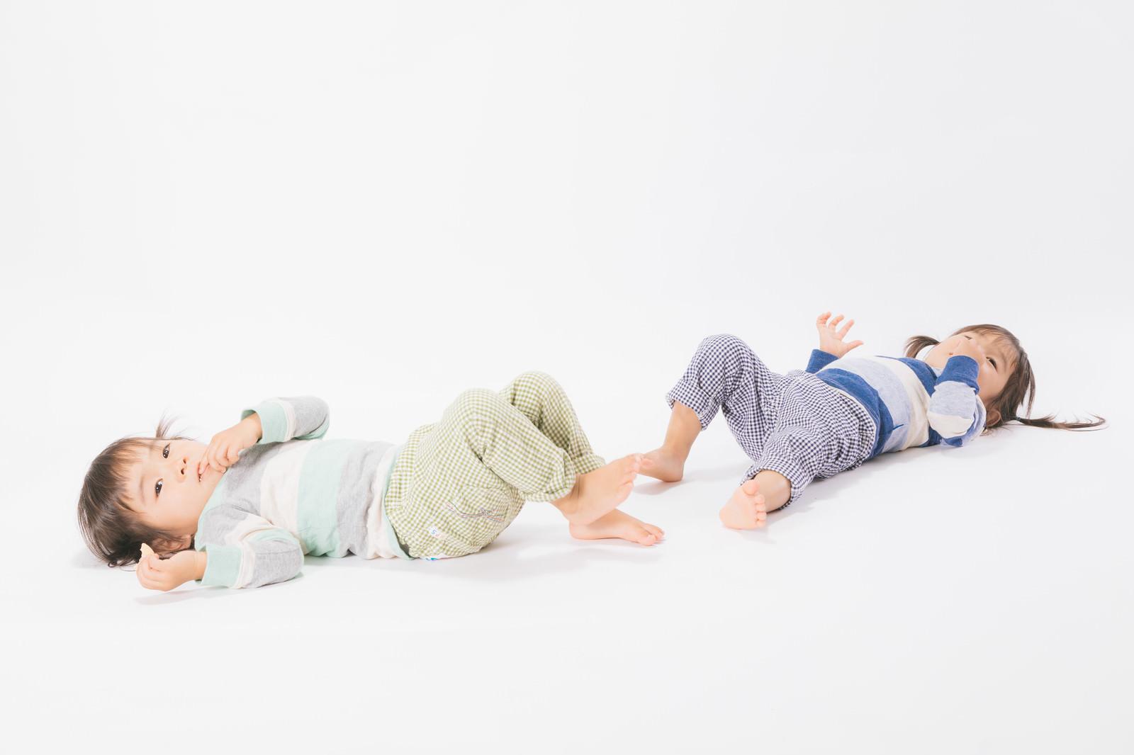 「寝そべる双子女児」の写真[モデル:あおみどり]