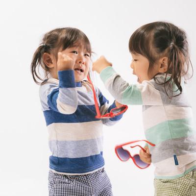 「ボカスカ取り合いの喧嘩をする双子姉妹」の写真素材