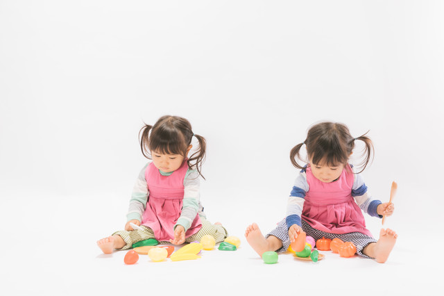 仲良くおままごとをする双子女児の写真