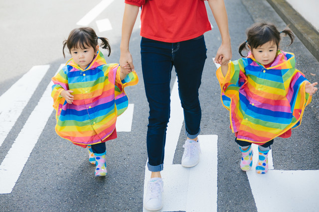 公道は危ないのでしっかり子供の手をにぎる母親の写真