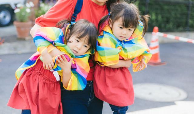 駄々をこねる双子と抱きかかえる母親の写真