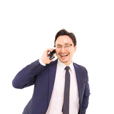電話しながら笑顔になるドイツ人ハーフの写真