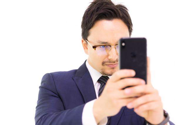 iPhone XS Max で縦写真を撮る男性会社員の写真