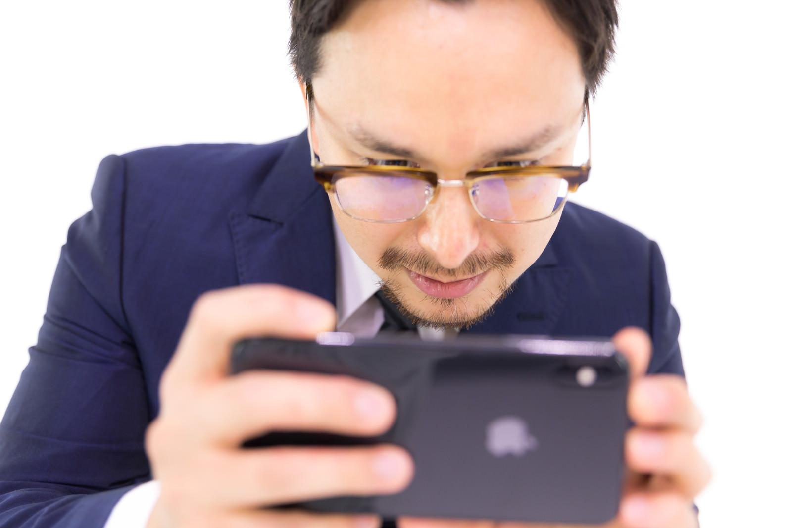 「iPhone XS Max で動画を見るビジネスマン」の写真[モデル:Max_Ezaki]