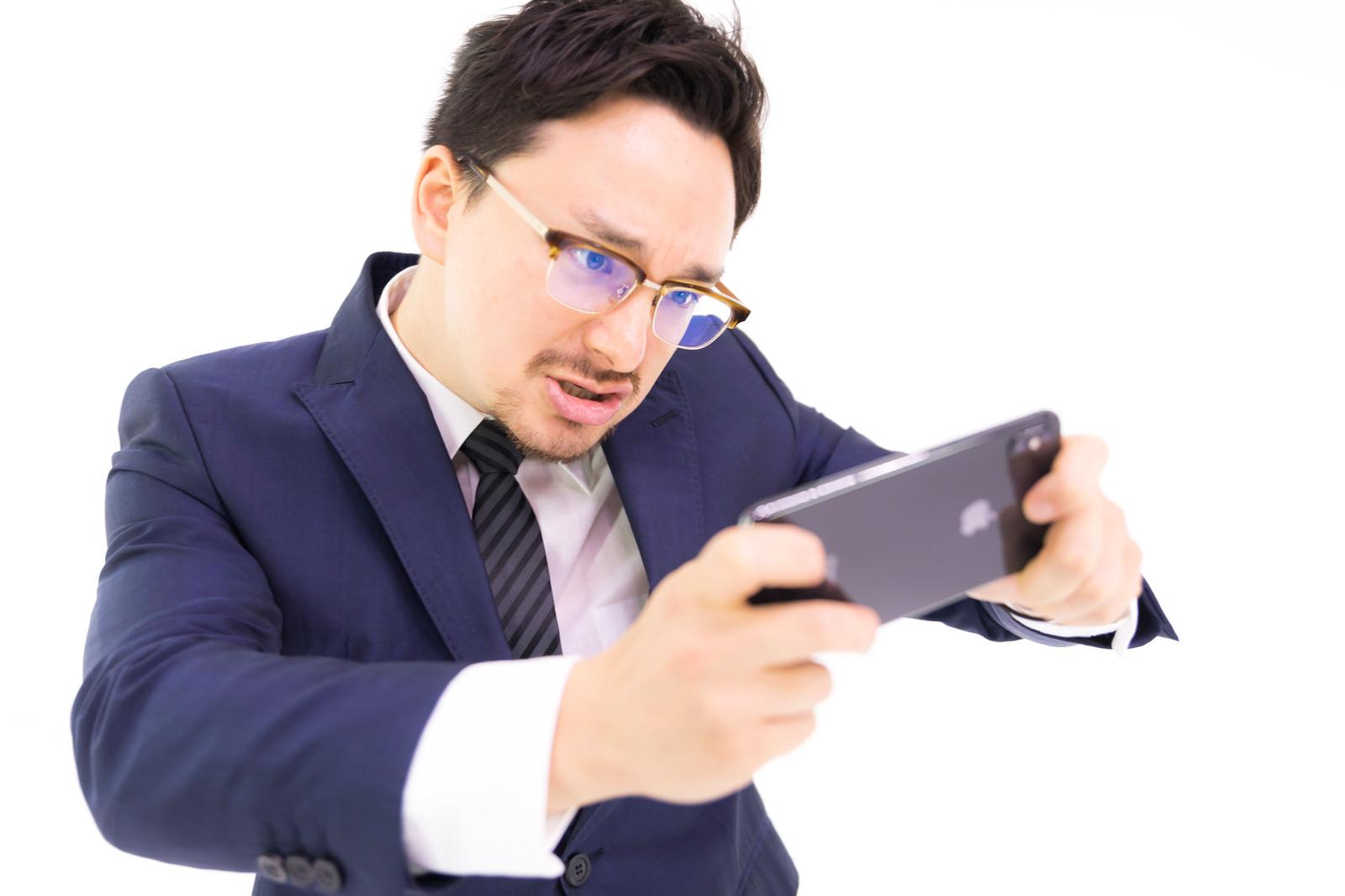 「iPhone XS Maxでレースゲームをプレイする会社員」の写真[モデル:Max_Ezaki]