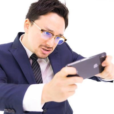 iPhone XS Maxでレースゲームをプレイする会社員の写真