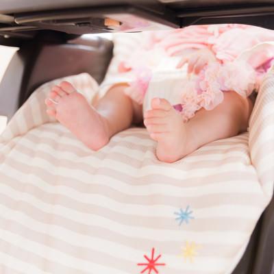 「ベビーチェアに座る赤ちゃんのムチムチあんよ」の写真素材