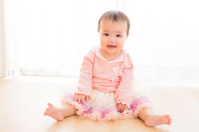 遊んでほしいとこちらを見つめる乳幼児の写真