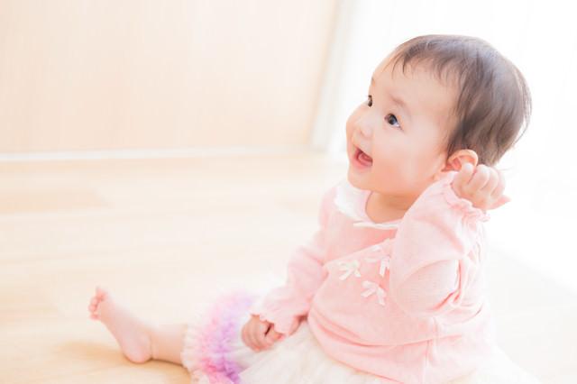 大人には見えない何かと笑顔で対話する赤ちゃんの写真
