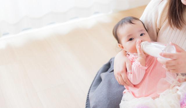 ママに抱かれて哺乳瓶でミルクを飲む赤ちゃんの写真