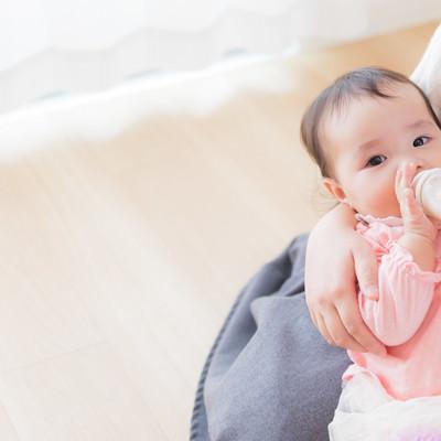 「ママに抱かれて哺乳瓶でミルクを飲む赤ちゃん」の写真素材