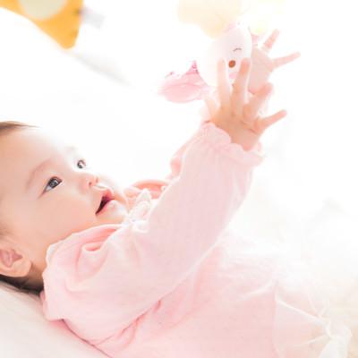 「ベッドメリーでごきげんな赤ちゃん」の写真素材