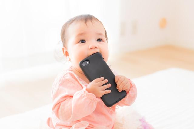 スマートフォンを口に入れてしまう赤ちゃんの写真