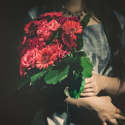 「バラの花束をを抱えた女性」の写真素材