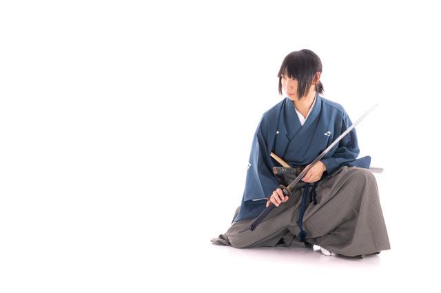 座った状態で刀を納める侍の写真