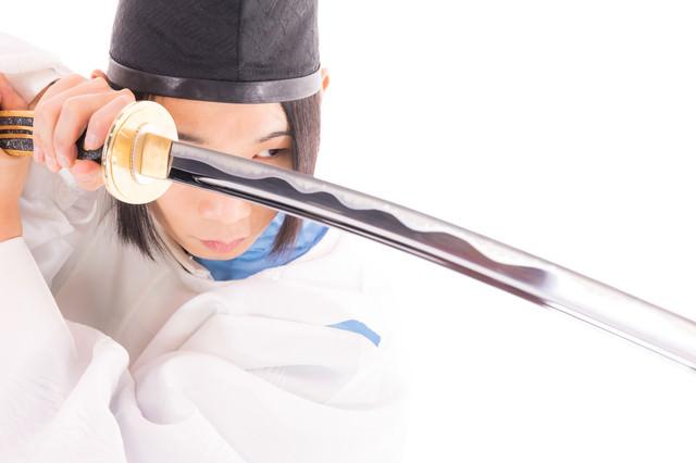 太刀を構え剣先を見つめる狩衣の剣士の写真