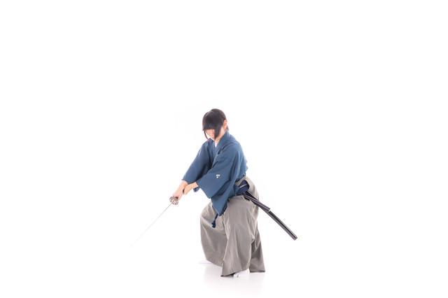 袈裟斬りする袴姿の侍の写真