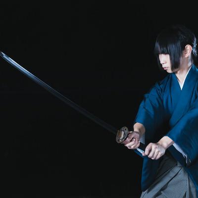 暗闇の中、抜刀する若い侍の写真