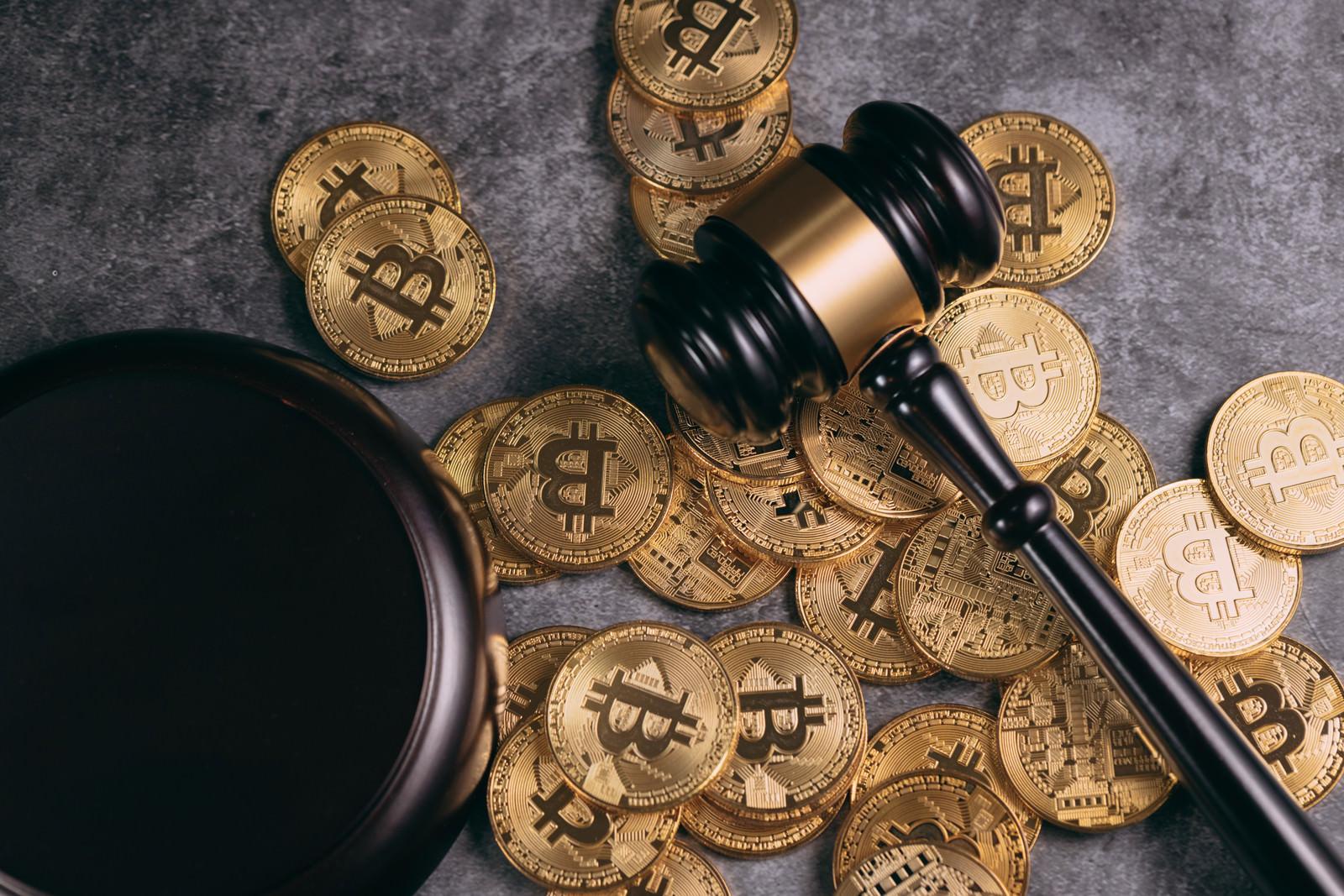 「散らばったビットコインとガベル(小槌)」の写真