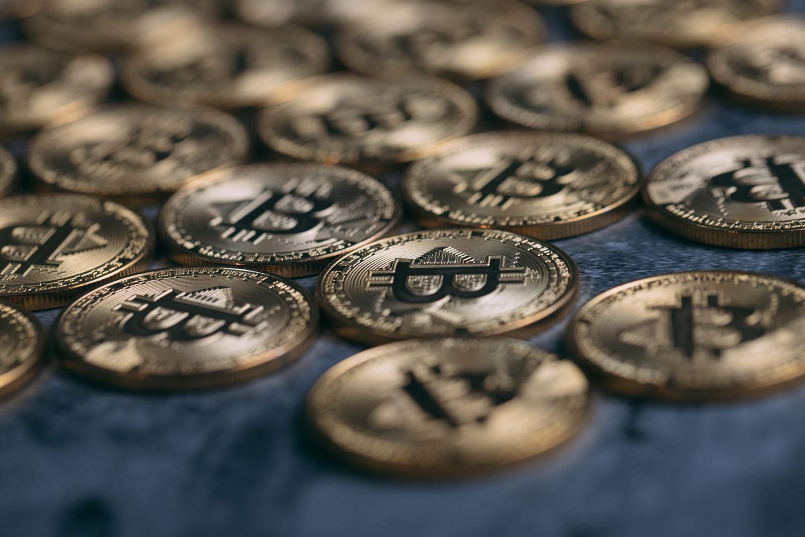 「卓上に散らばる金貨(ビットコイン)」の写真