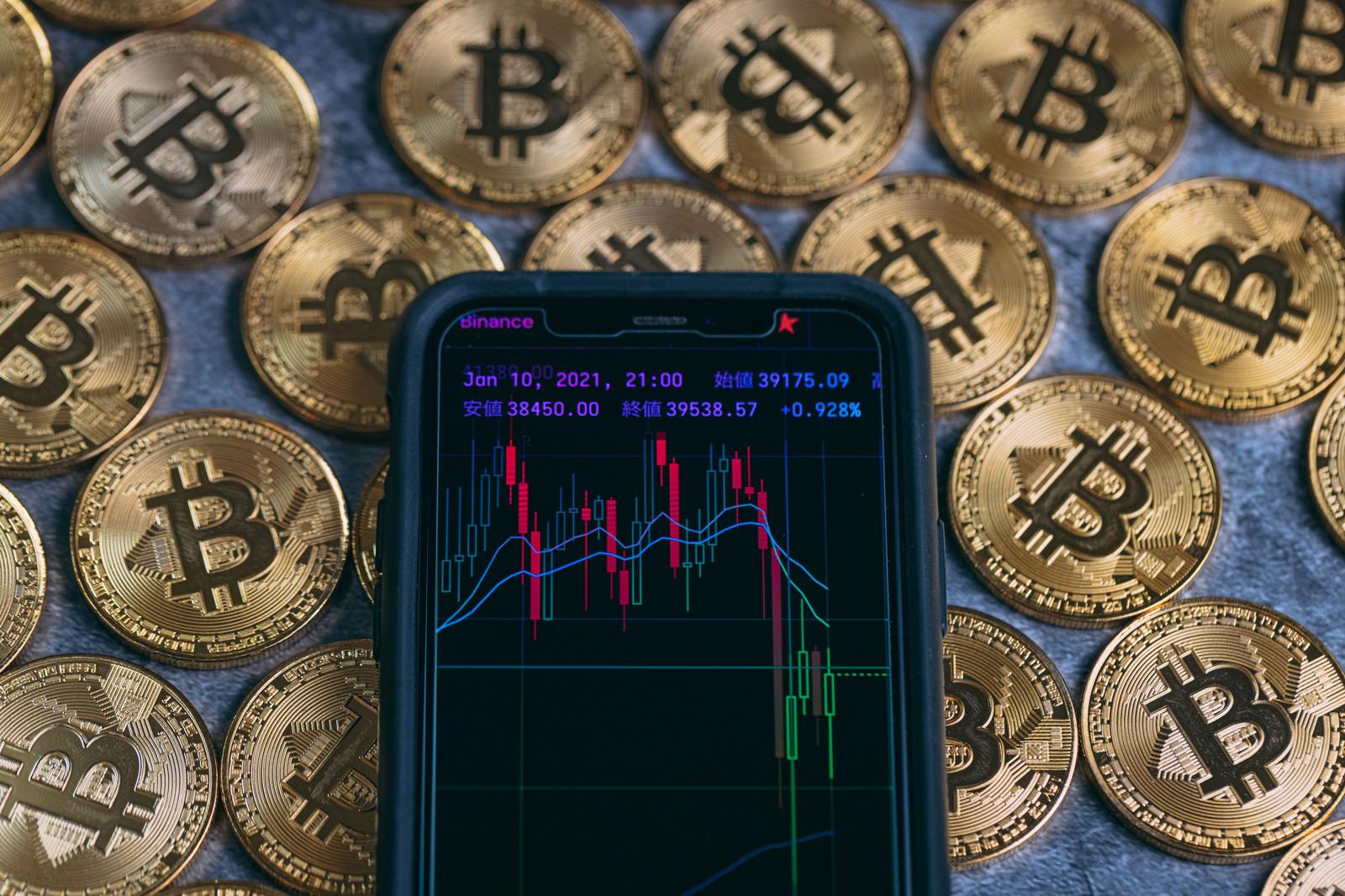 「スマホのトレード画面とビットコイン」の写真