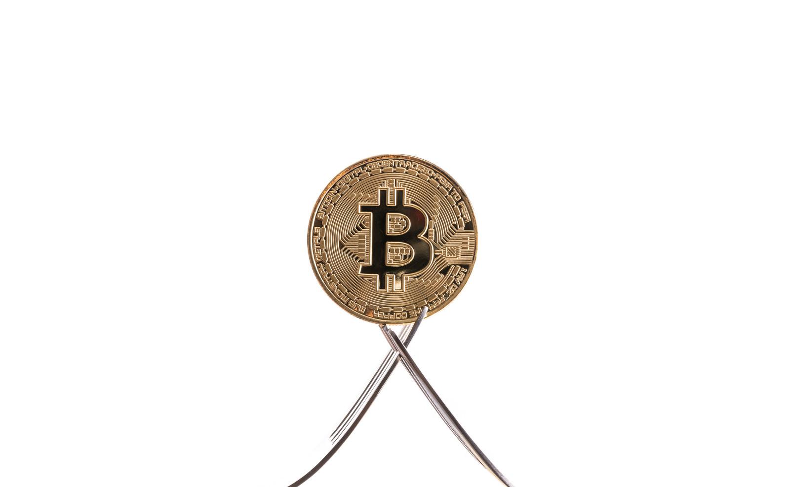 「フォークで挟まれるビットコイン」の写真