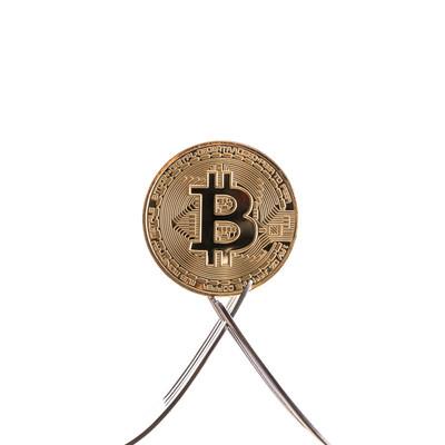 フォークで挟まれるビットコインの写真