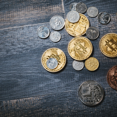 散らばったビットコインと貨幣の写真