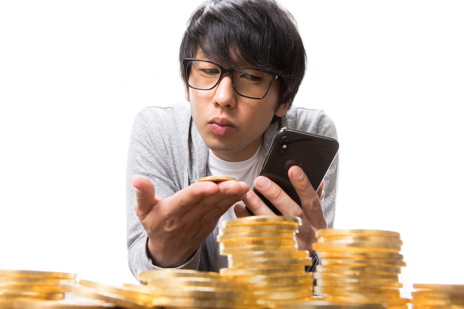 「仮想通貨の価格をスマホでチェックする男性投資家」の写真[モデル:大川竜弥]