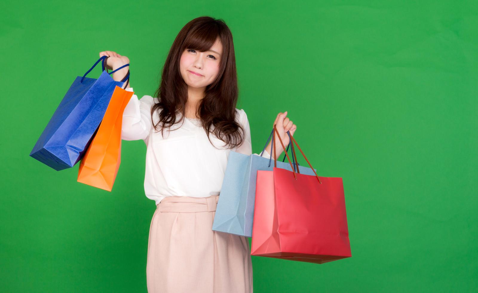 「買い物しすぎて困り顔の女性」の写真[モデル:河村友歌]