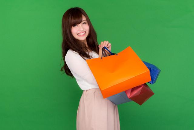 ブラックフライデーの大規模な安売りで両手いっぱいに買い物をする女性の写真