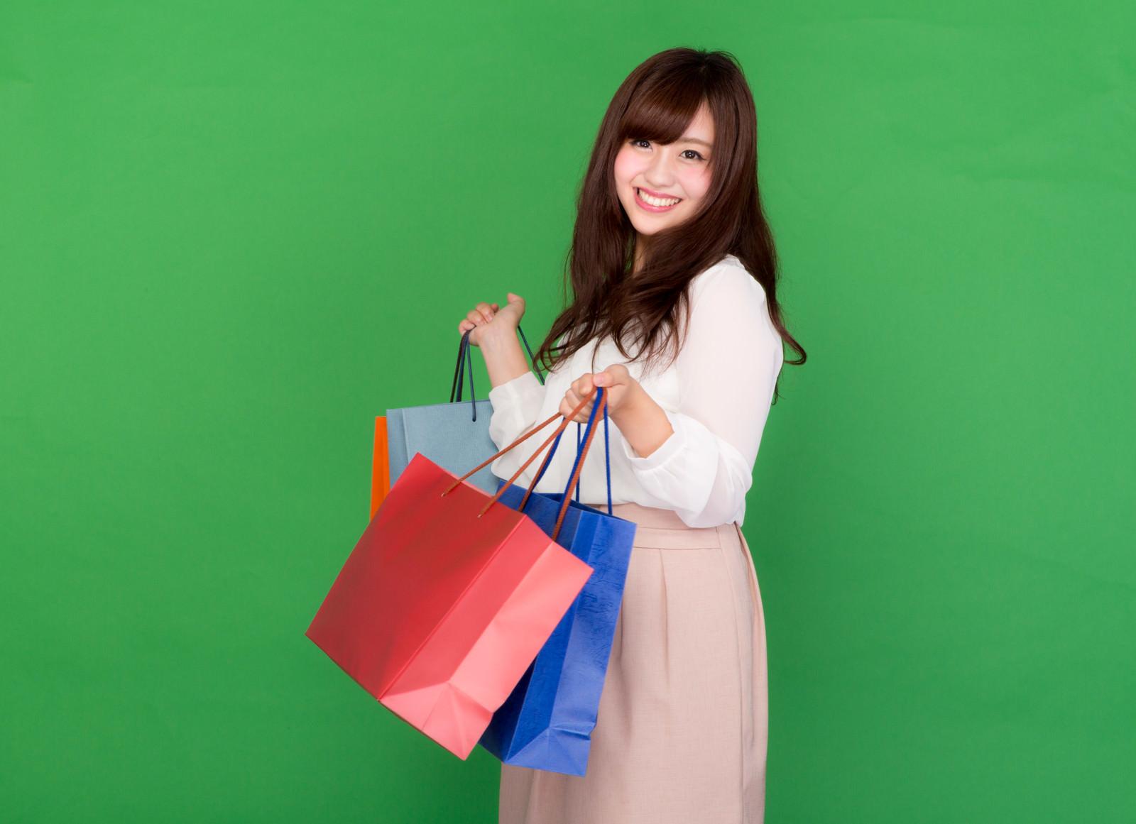 「ブラックフライデーのセールで大量に買い物をする女性」の写真[モデル:河村友歌]
