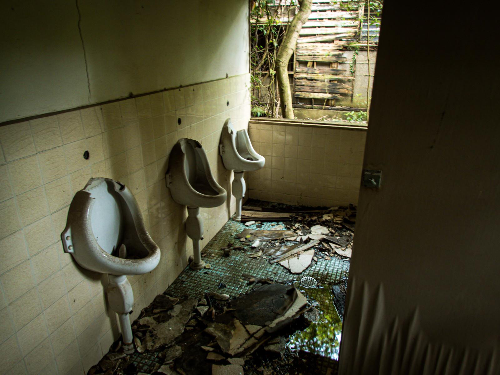「ぼろぼろに朽ち果てたトイレ(男性用)」の写真