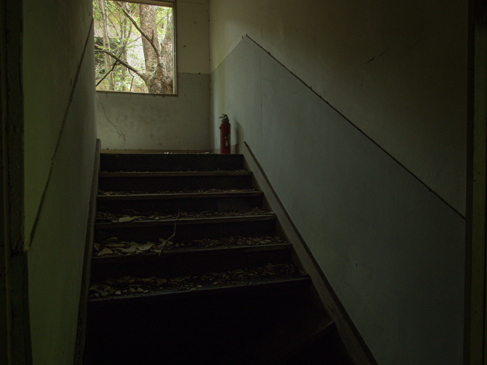 「廃墟の階段とその上にある消化器」の写真
