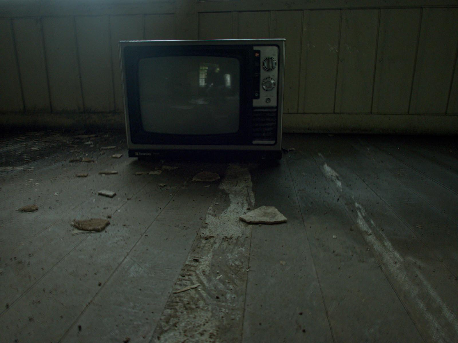 「廃屋にぽつんと置かれた古いカラーテレビ」の写真