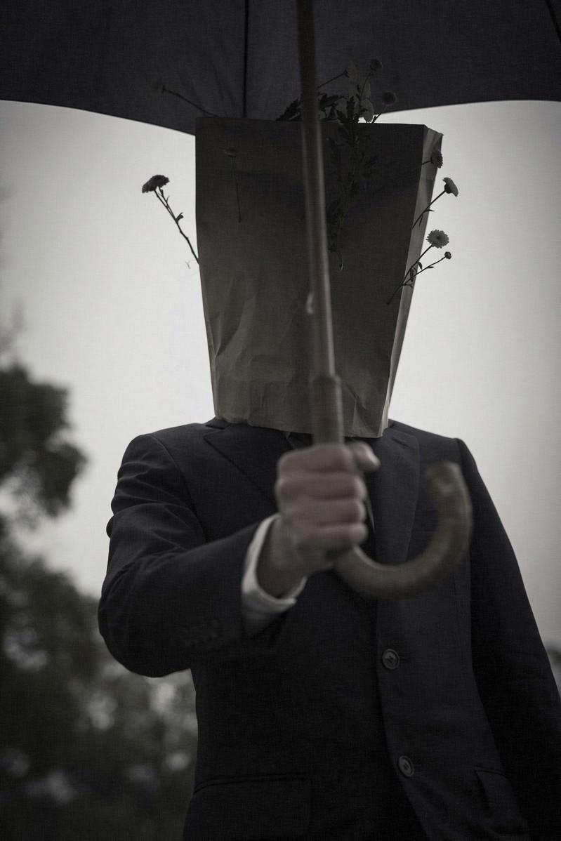 「傘を手渡す紙袋紳士」の写真
