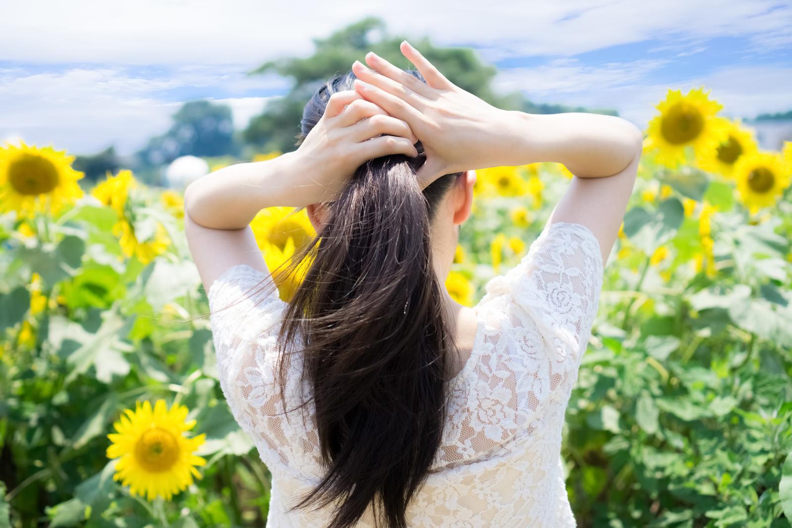 「暑くて後ろに髪を束ねる女性」の写真