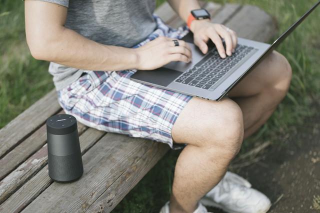 公園のベンチで音楽を流しながら作業するエンジニアの写真
