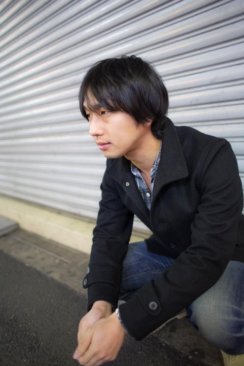 「閉まったシャッターの前で座り込む男性」の写真[モデル:大川竜弥]