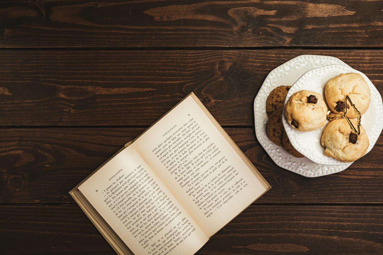「卓上に置かれた読みかけの洋書とクッキー」の写真