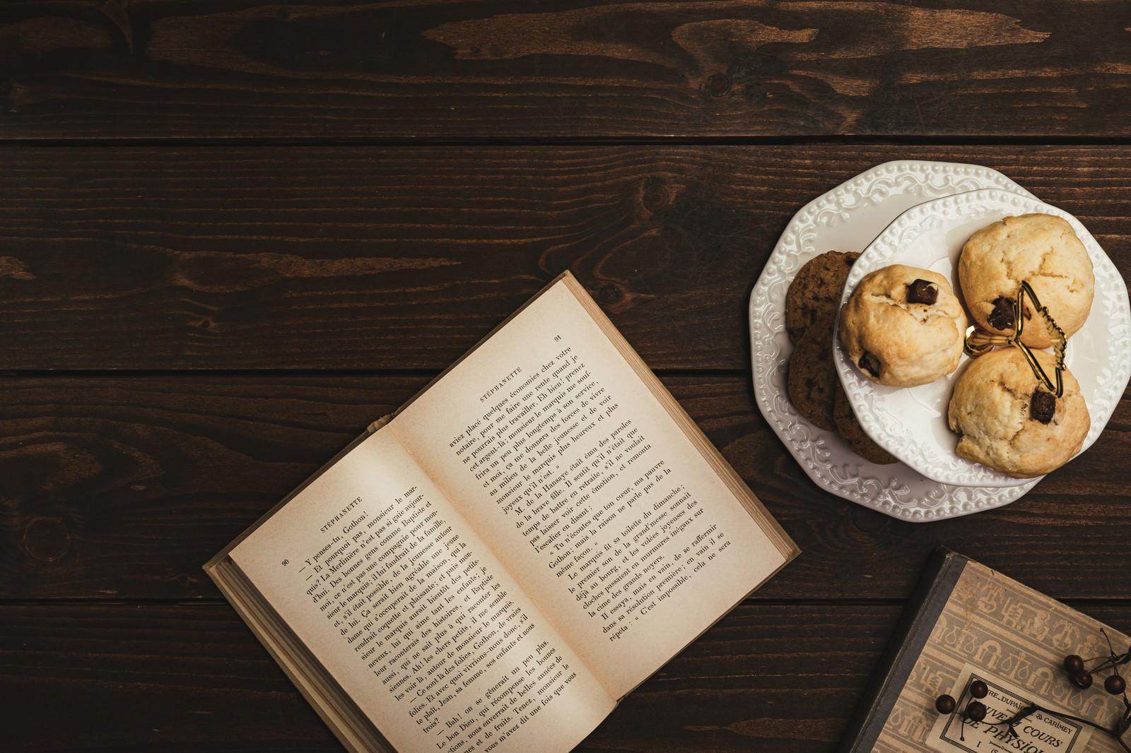 「テーブルに置かれた洋書とクッキー」の写真