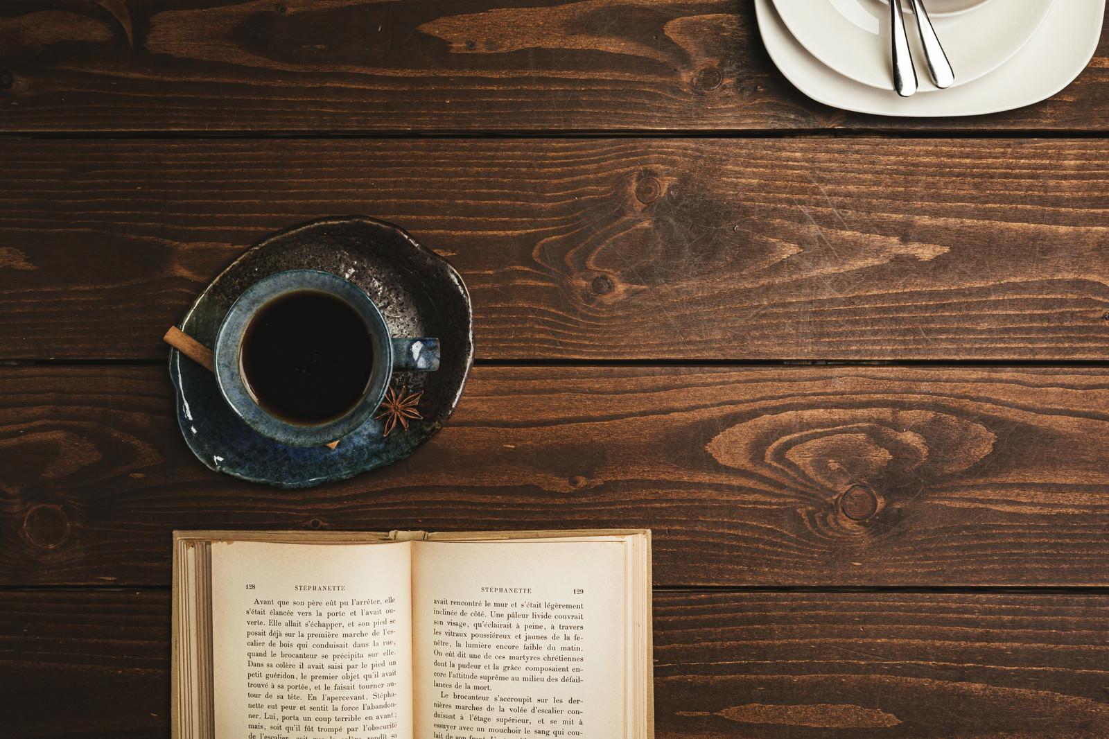 「喫茶店のテーブルに置かれた洋書とコーヒー」の写真