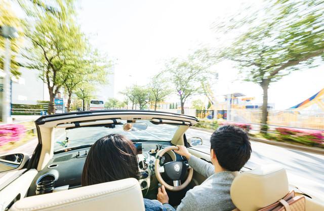 街中をオープンカーで颯爽と駆け抜ける(デート中)の写真