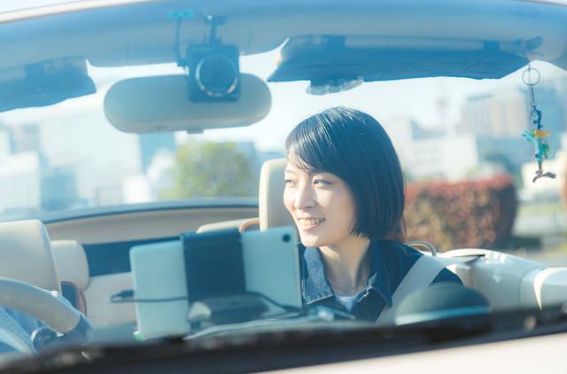 オープンカーの助手席で微笑む彼女の写真